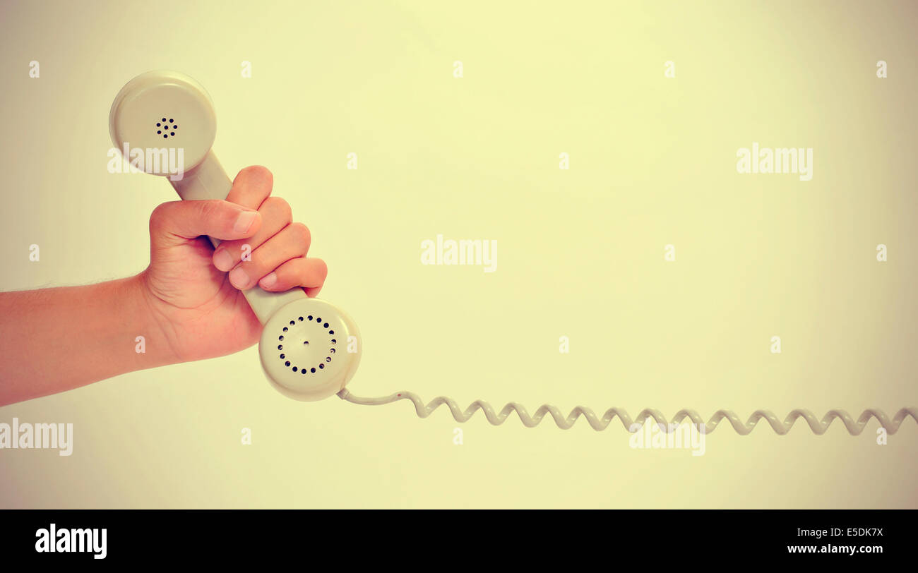 a man hand holding the handset of a telephone, with a retro effect - Stock Image