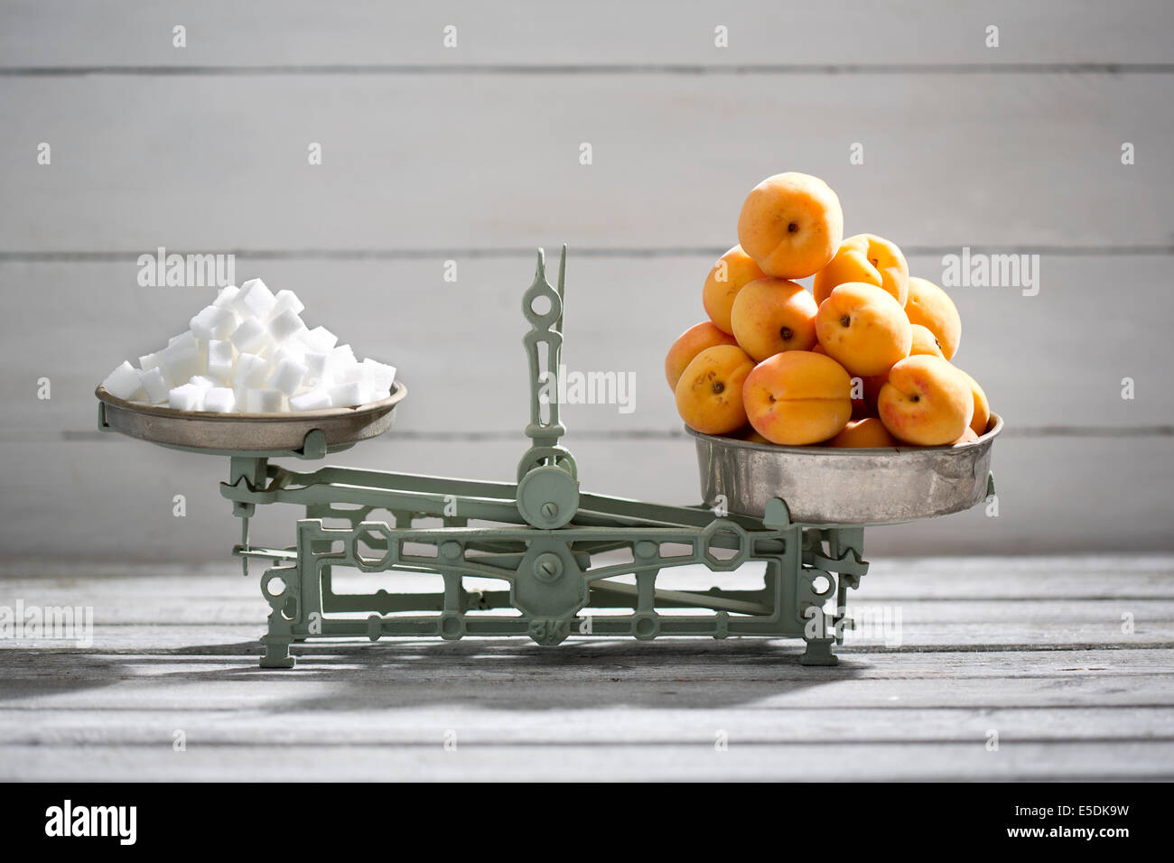 Apricots and sugar cubes on a scale - Stock Image