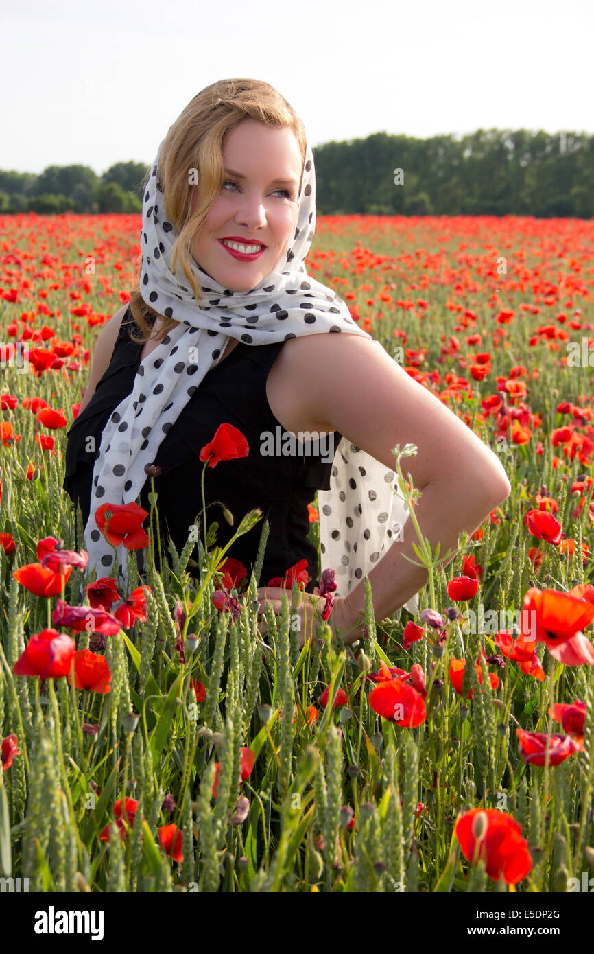 Portrait of smiling woman dressed in twenties style standing in poppy field - Stock Image