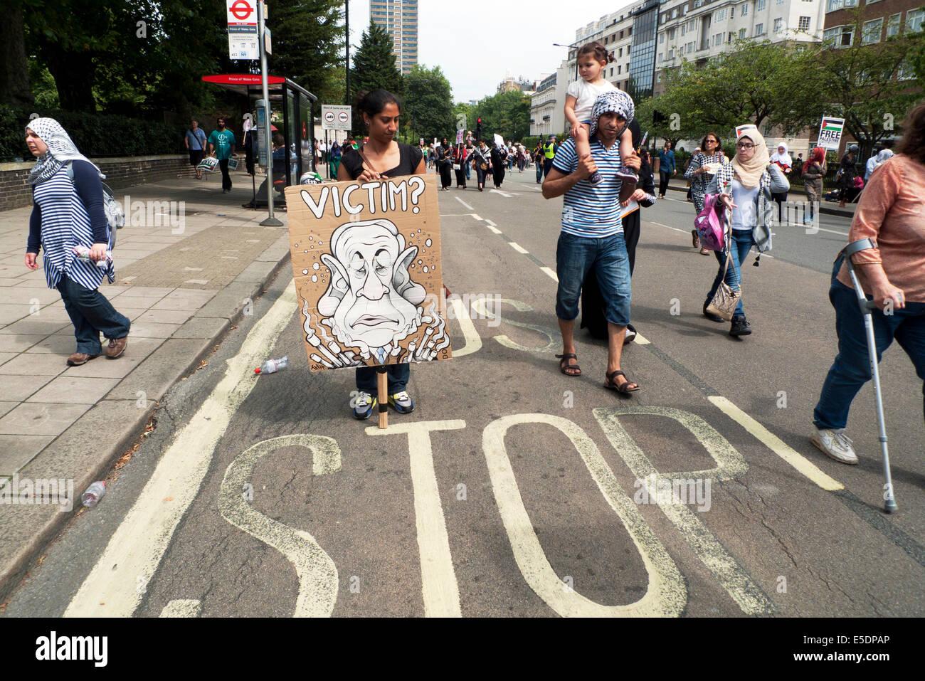 A Palestinian woman holding a Benjamin Netanyahu placard at Palestine Anti War Demonstration London 19th July 2014 - Stock Image