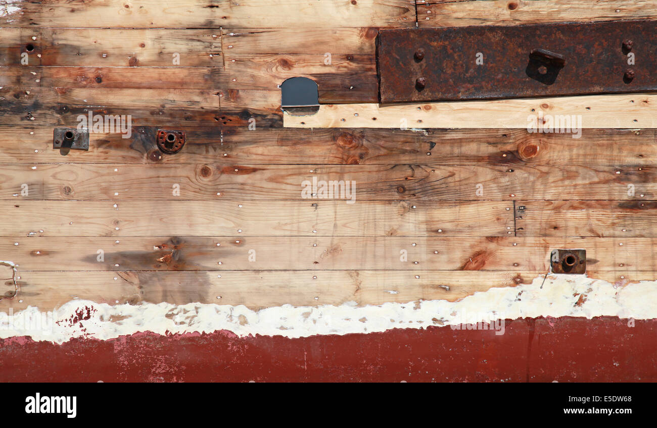 Old wooden ship fragment, hull under renovation, background