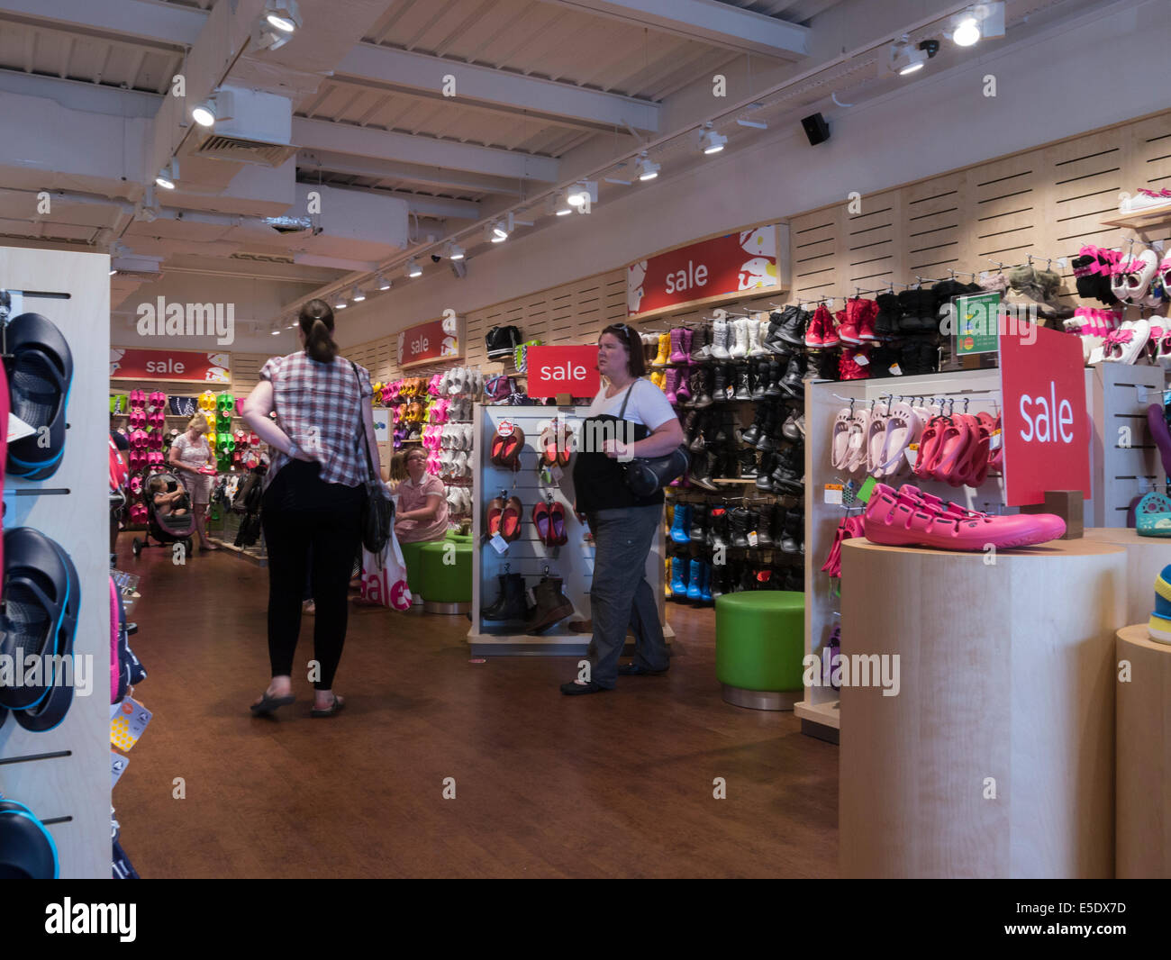 Customers in store selling Croc products with sale on - Stock Image