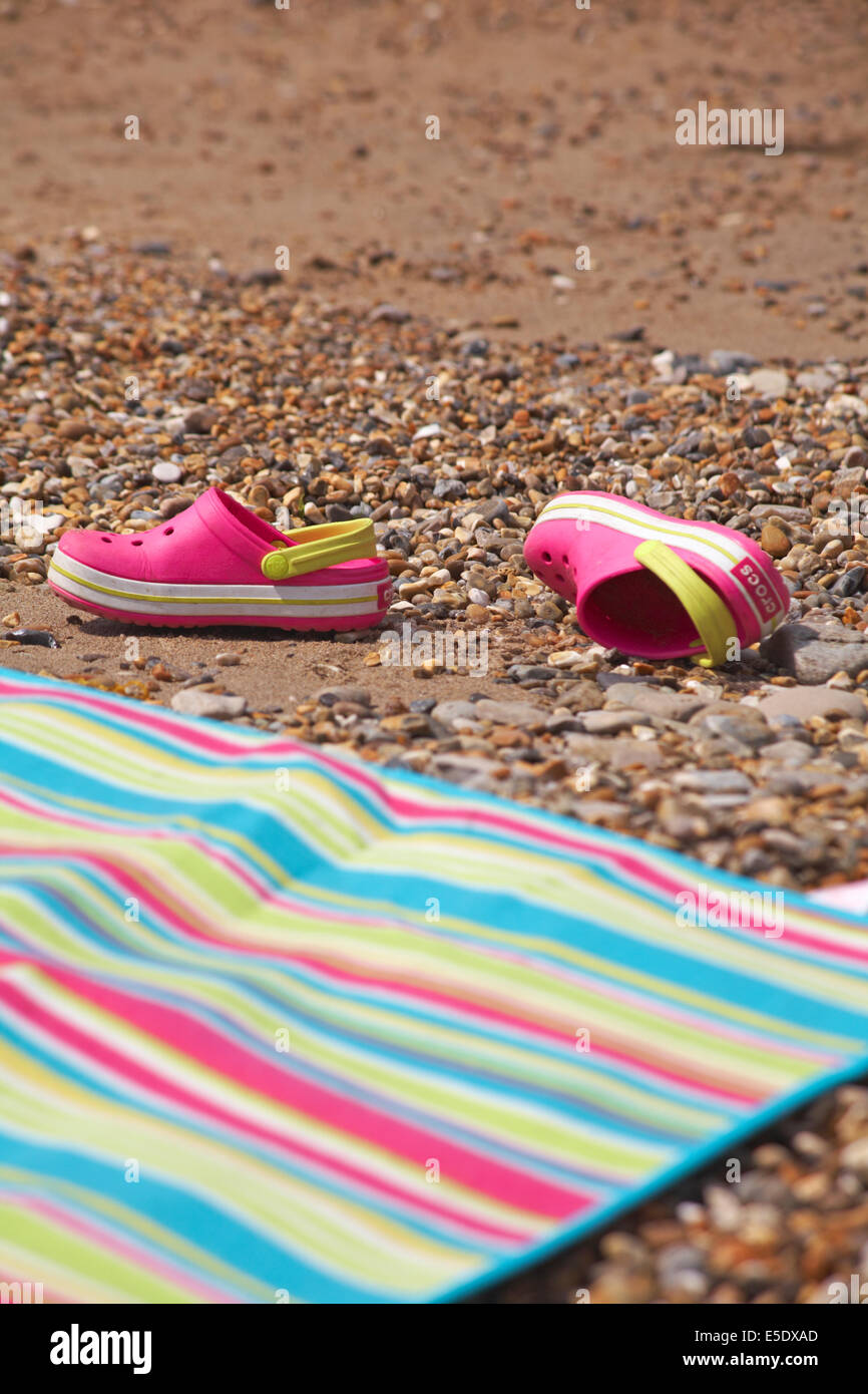 d967bf64a20e5 pink crocs discarded on beach next to stripey beach towel - Stock Image