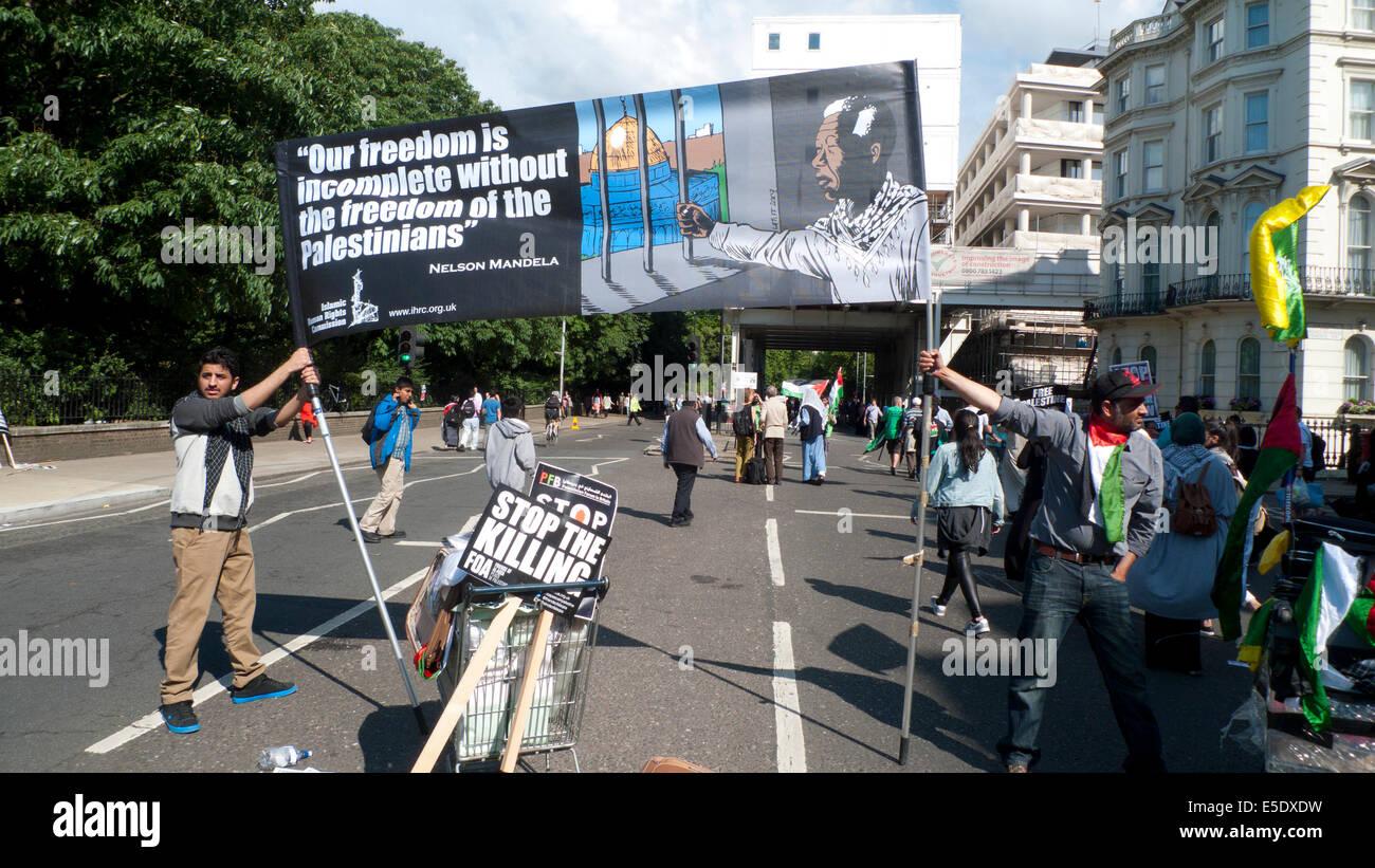 After Palestinian protest against Israeli bombing in Gaza men hold up Nelson Mandela freedom banner, London .2014 - Stock Image