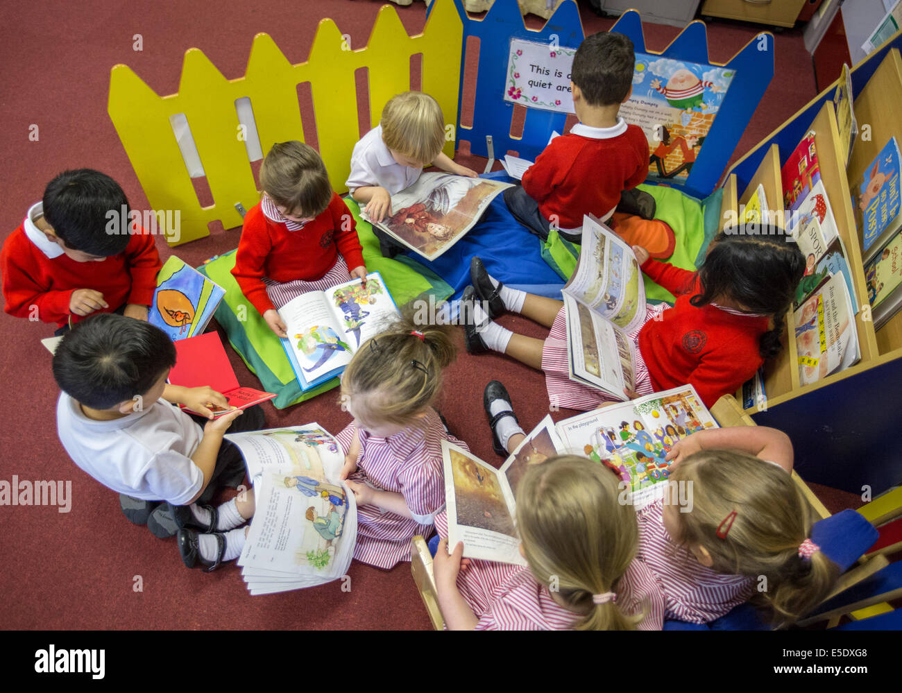 Primary school children reading in a classroom in the UK. - Stock Image