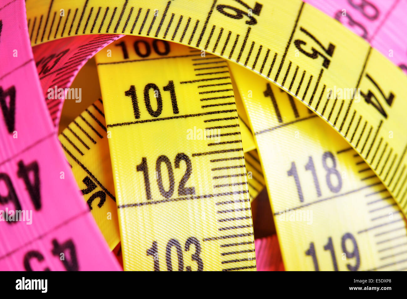 Yellow and pink measuring tapes close up Stock Photo