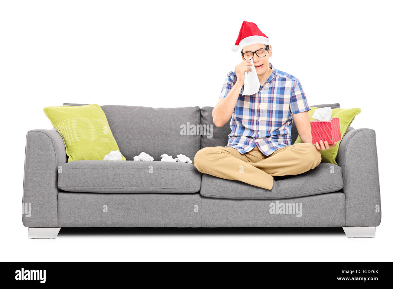 Sad man with Santa hat wiping his eyes from crying - Stock Image
