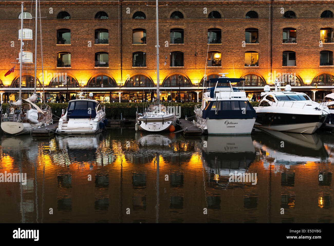 Boats and reflections in St Katharine Docks at sunset. St Katharine Docks, in the London Borough of Tower Hamlets Stock Photo