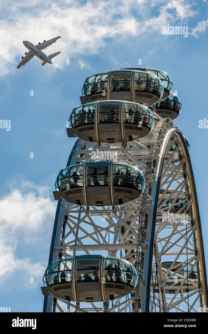 A plane passes over the London Eye, a giant Ferris wheel on the South Bank of the River Thames in London - Stock Image
