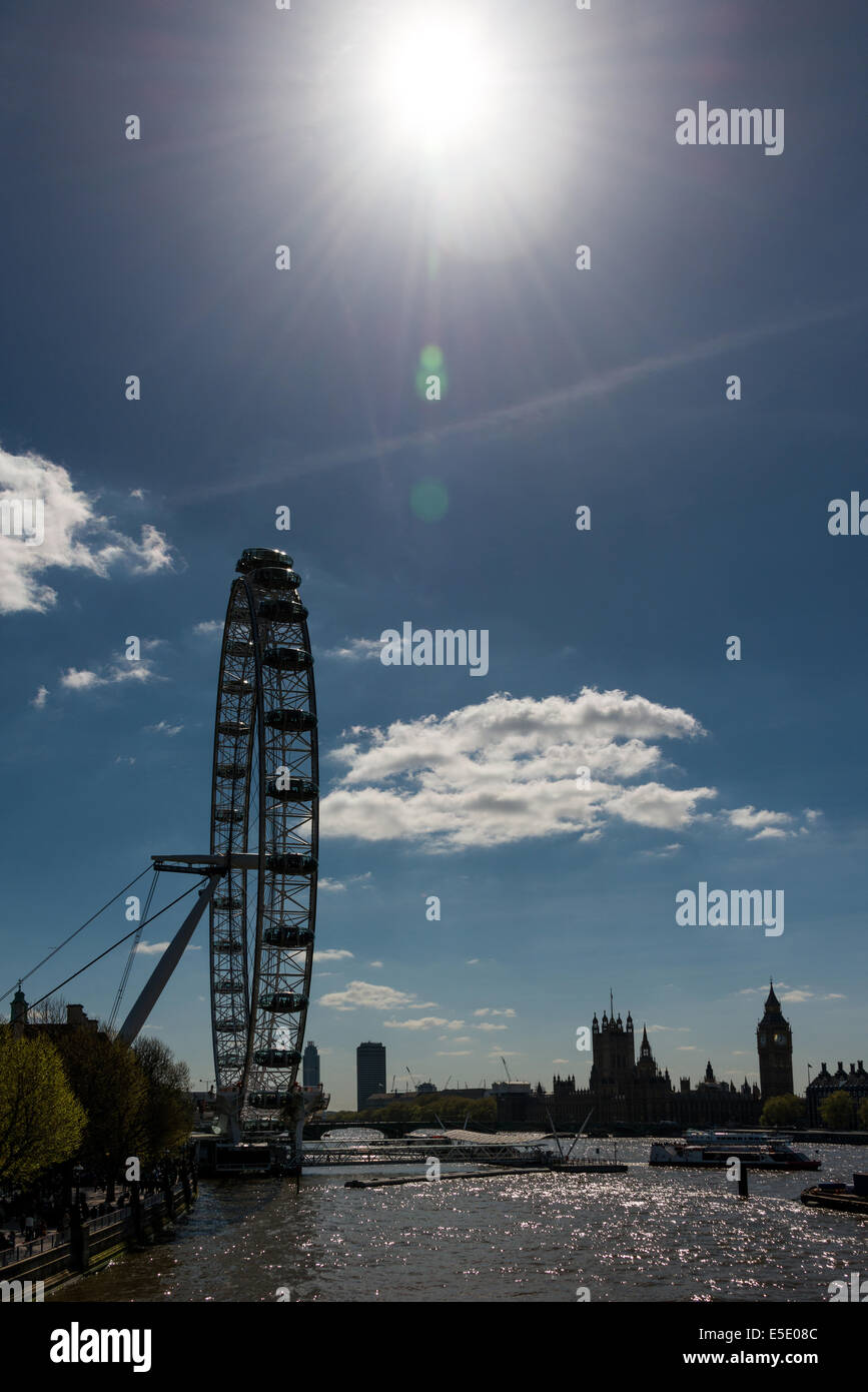 The sun shining over the London Eye, a giant Ferris wheel on the South Bank of the River Thames in London - Stock Image