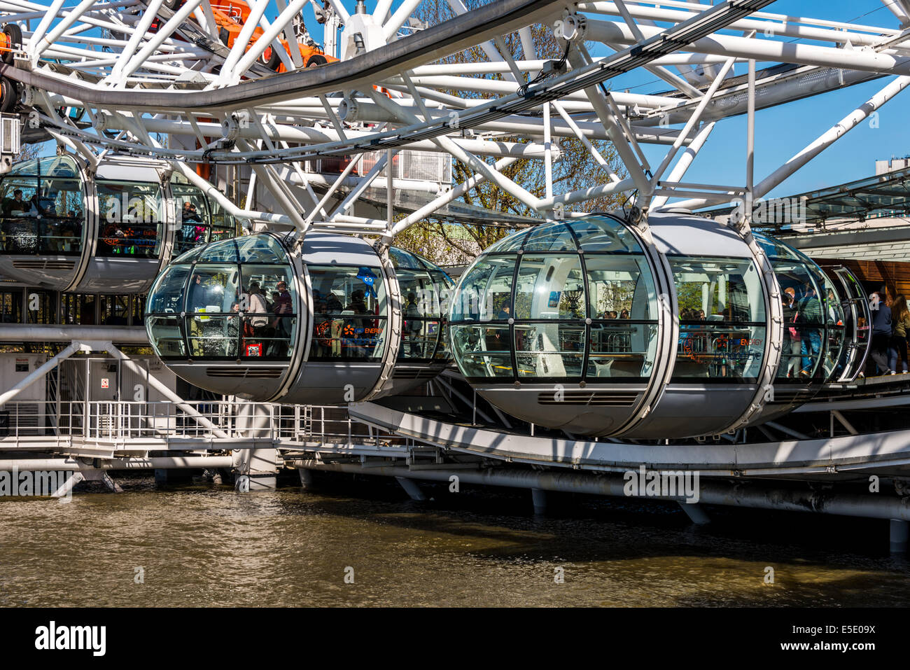 Passengers starting their journey on The London Eye, a giant Ferris wheel on the South Bank of the River Thames - Stock Image