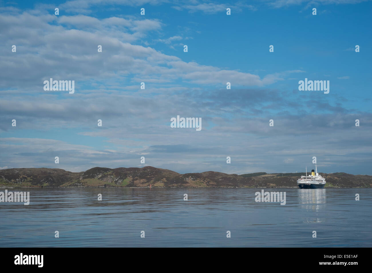 Cruise ship moored, Stornoway harbour, Isle of Lewis, Outer Hebrides on bright blue sea with blue skies - Stock Image