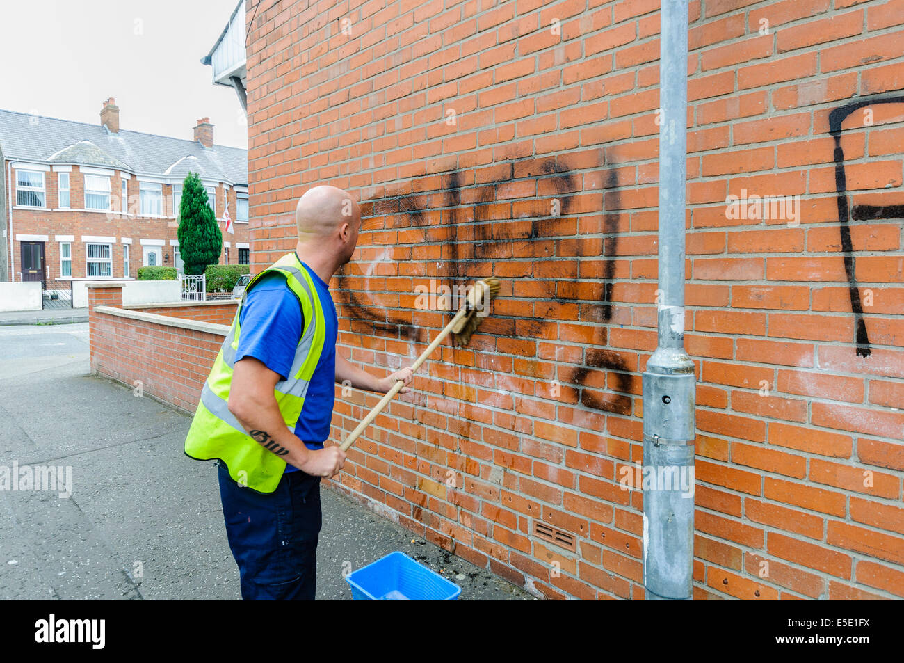 Belfast, Northern Ireland. 29th July, 2014. A council worker removes graffiti saying 'C18' [Combat 18] spraypainted - Stock Image
