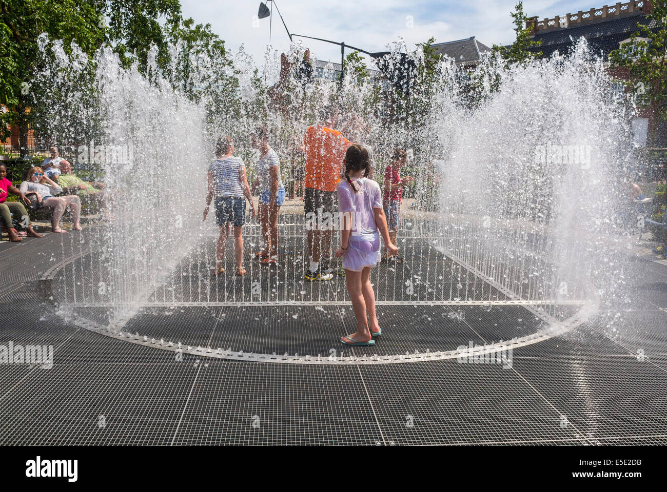 Amsterdam, Holland, Tourist Children Cooling off in Public Garden Fountains during Summer Heat Spell Stock Photo