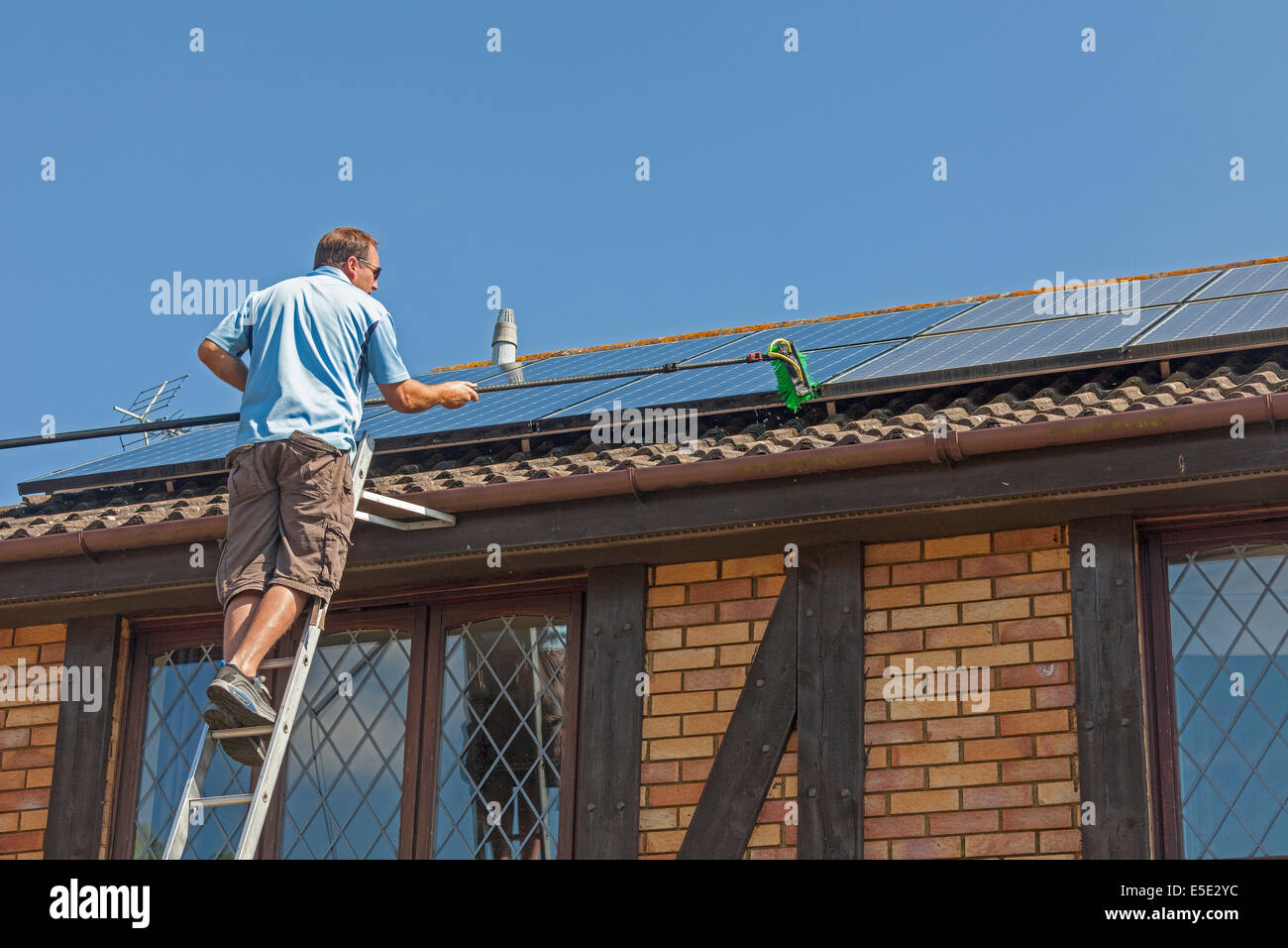 Cleaning accumulated dirt, grime and bird droppings from rooftop Photovoltaic (PV) solar panels. JMH6245 - Stock Image
