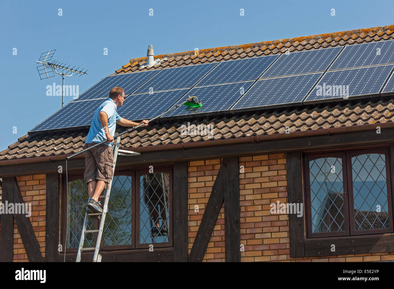 Cleaning accumulated dirt, grime and bird droppings from rooftop Photovoltaic (PV) solar panels. JMH6246 - Stock Image