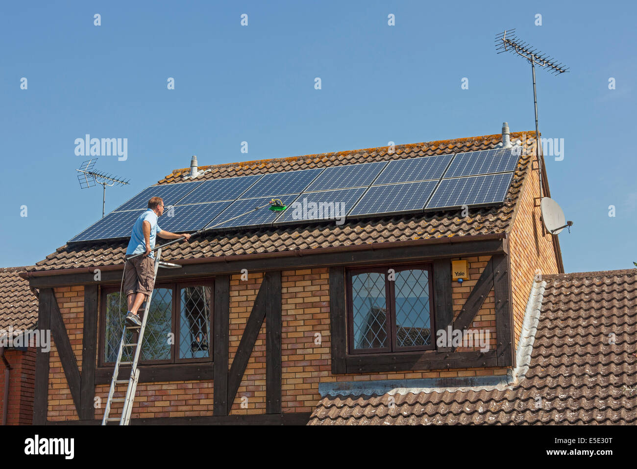 Cleaning accumulated dirt, grime and bird droppings from rooftop Photovoltaic (PV) solar panels. JMH6247 - Stock Image