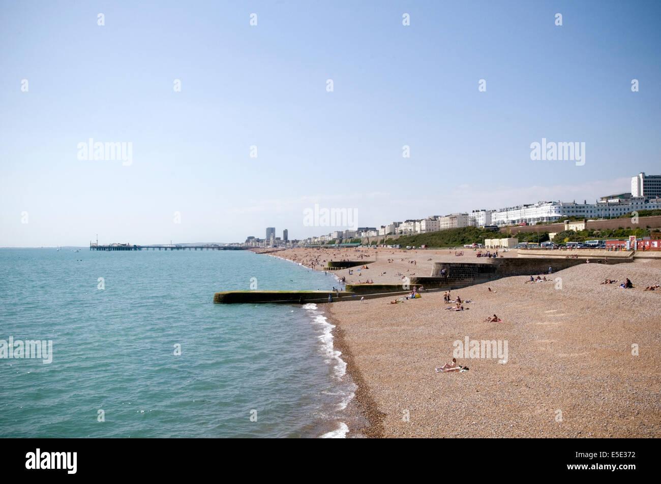 brighton beach summer weather hot sunny uk shale stone stoney beaches breakwater breakwaters break water waters - Stock Image