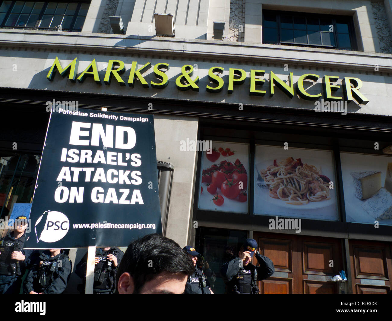 People demonstrating outsie M&S store against killing bombing of Gaza Palestinians by Israel  London UK 19.7.2014 - Stock Image