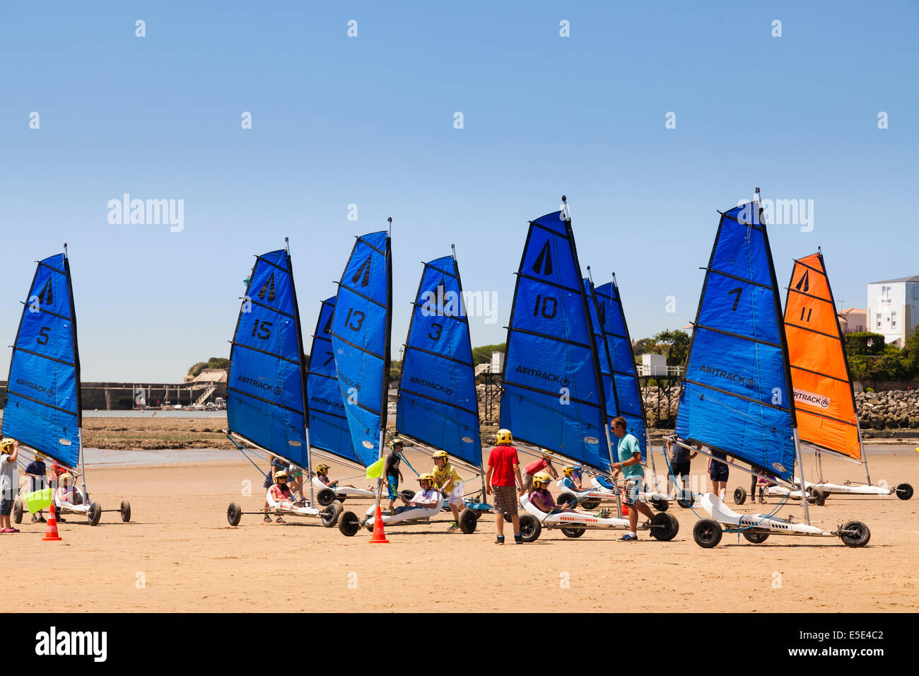 Group of children learning sand yachting on a beach. - Stock Image