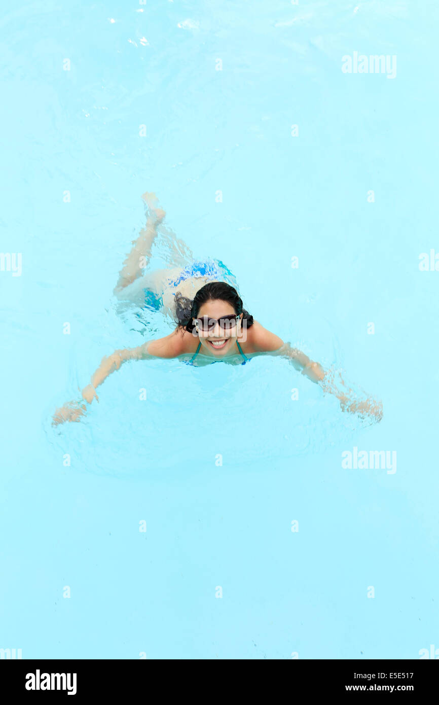 A happy young woman in a swimming pool - Stock Image