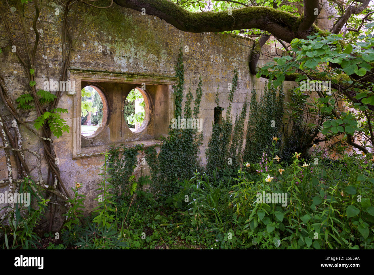 One of the three pairs of oval, spectacle-like windows in the garden wall of Stanway House, Stanway, Gloucestershire - Stock Image