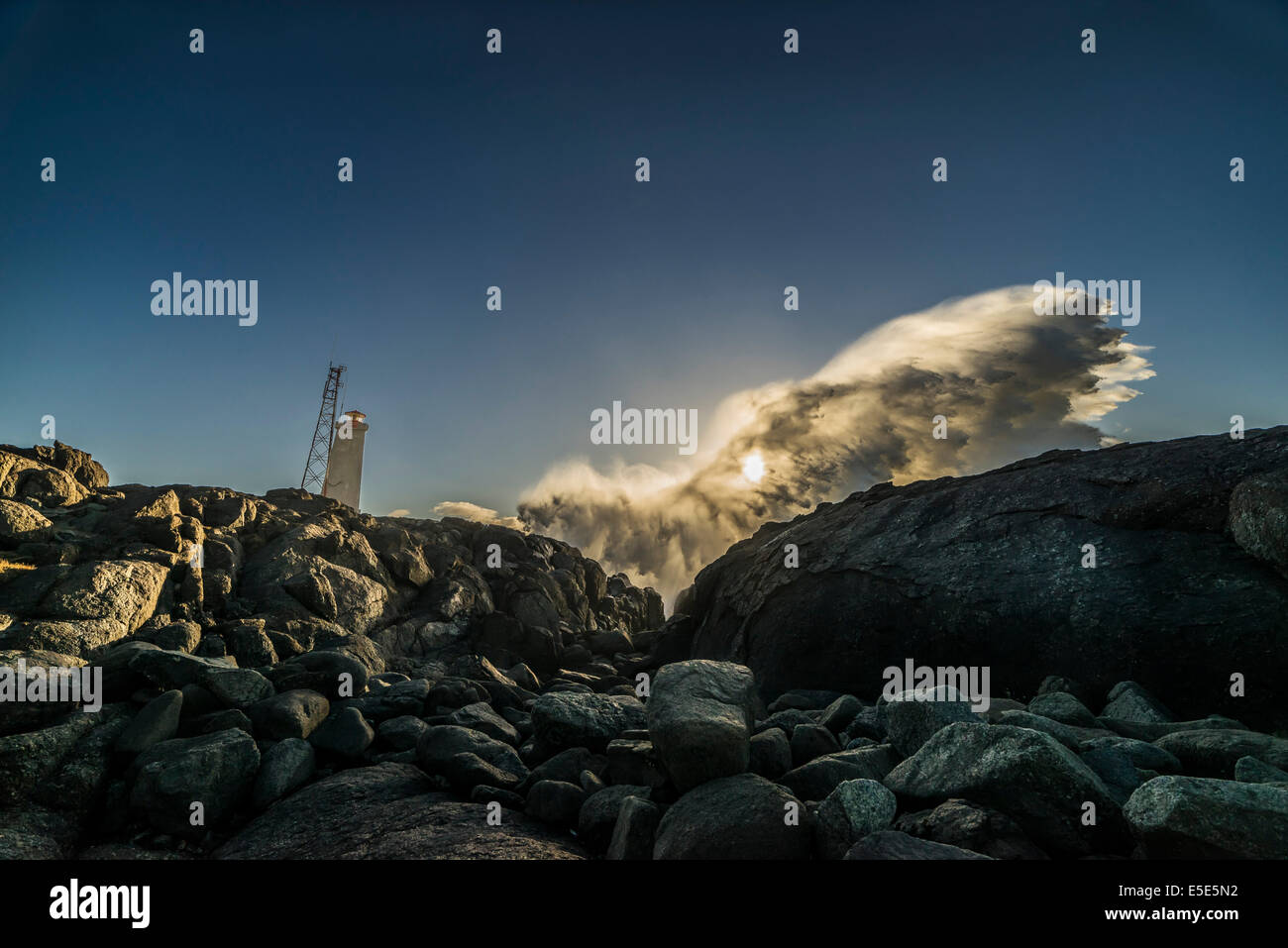 Lighthouse and waves crashing, Stokksnes by Hofn in Hornafjordur, Iceland - Stock Image