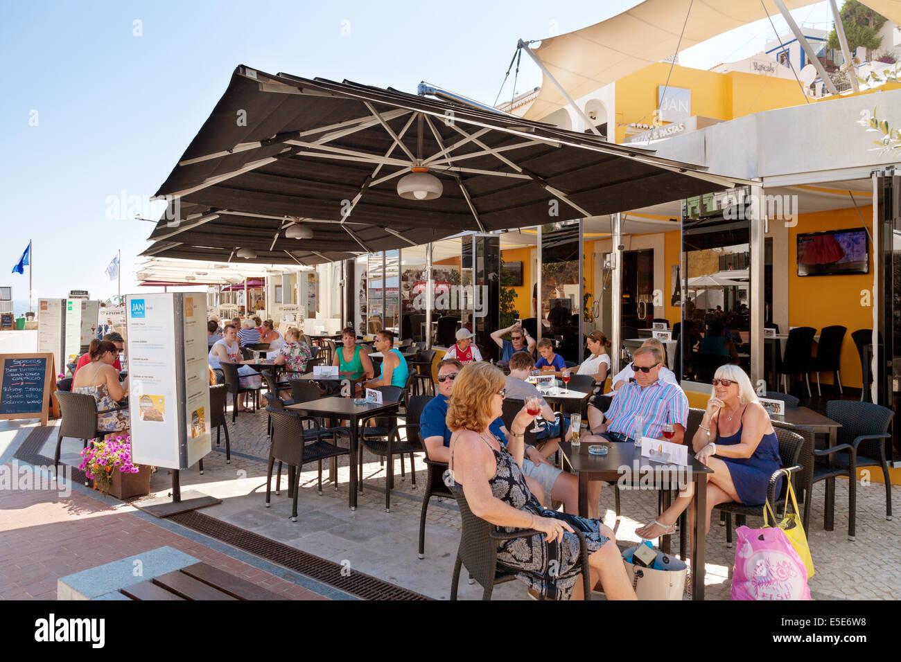 People on summer holiday drinking at a street cafe, Carvoeiro, Algarve Portugal, Europe Stock Photo