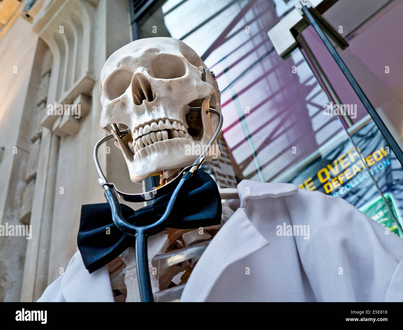 Humorous visual reminder of personal health care with human skeleton dressed as a Doctor Death with stethoscope - Stock Image