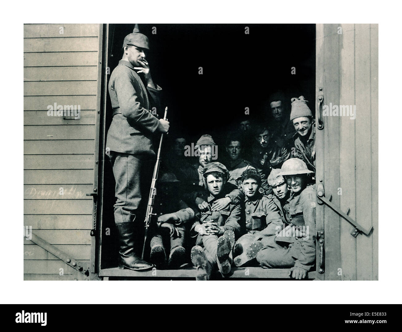 World War One captured British soldiers in railway carriage being guarded by German soldier wearing typical spiked Stock Photo