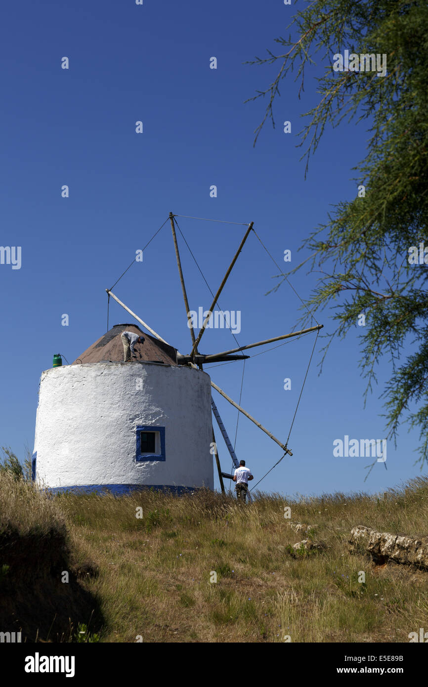 Workmen restoring old windmill in Portugal - Stock Image