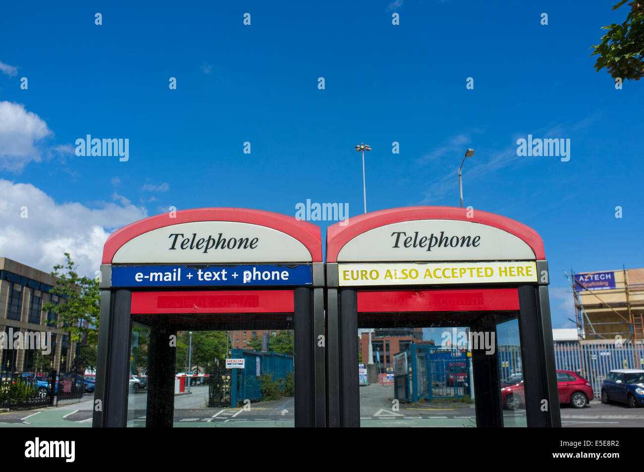 BT telephone boxes against a blue sky - Stock Image
