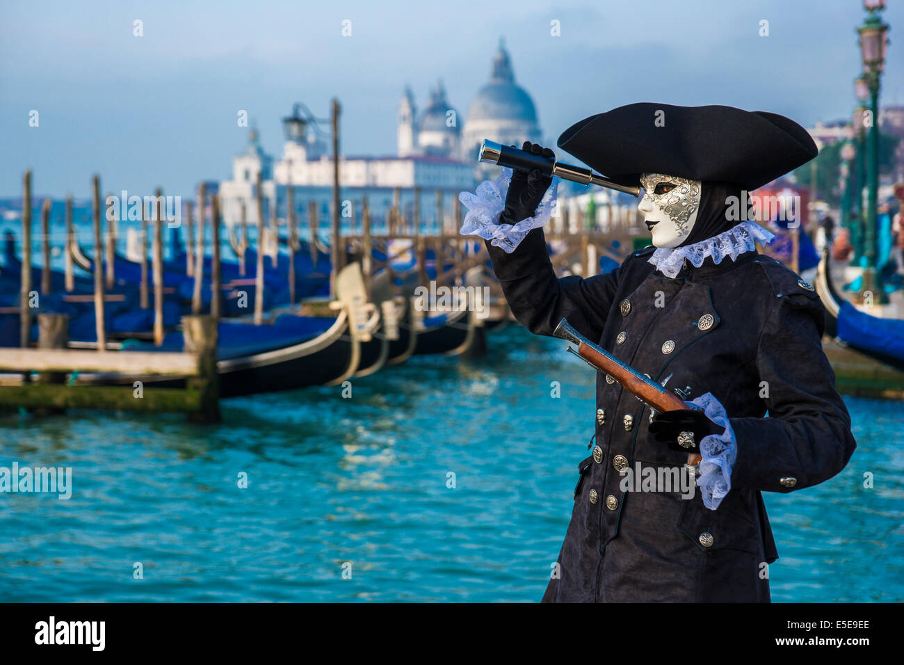 Carnival sea captain in black looks through telescope on the waterfront of the Lagoon of Venice . - Stock Image