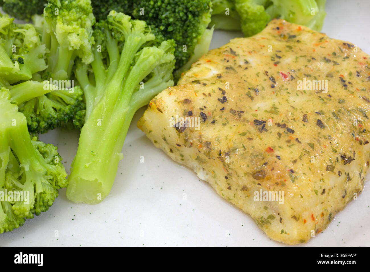 Close view of a fillet of baked pollock on a plate with broccoli. - Stock Image