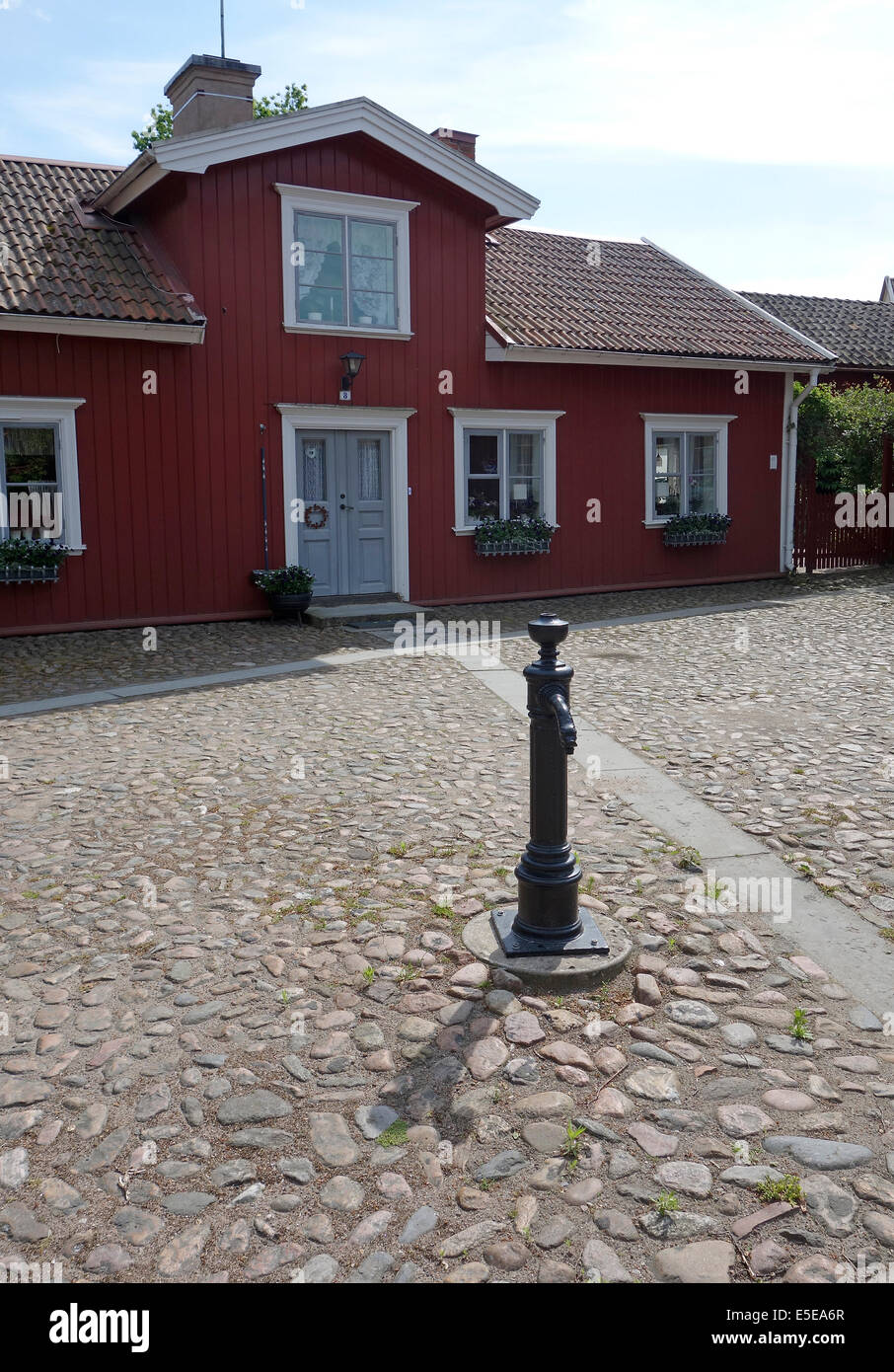 Public water tap in the middle of cobbled square of Old Lidköping. Sweden. - Stock Image