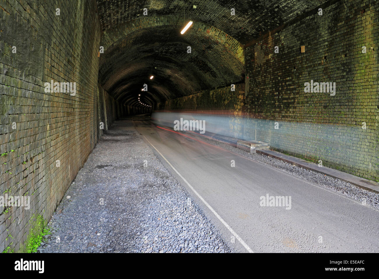 Cyclists motion blur in Litton Tunnel on the Monsal Trail, Derbyshire, Peak District National Park, England, UK. - Stock Image