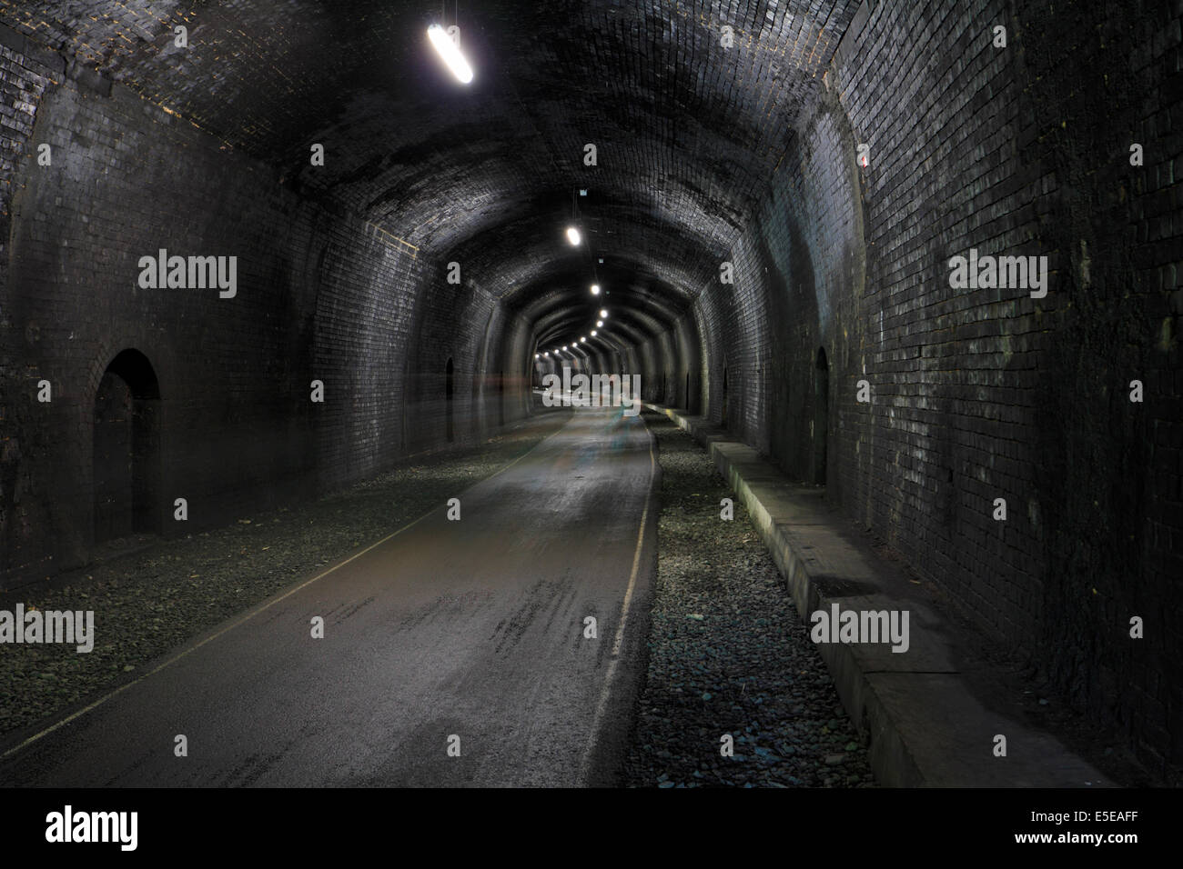 Cyclists motion blur in Headstone Tunnel on the Monsal Trail Derbyshire Peak District National Park England UK - Stock Image
