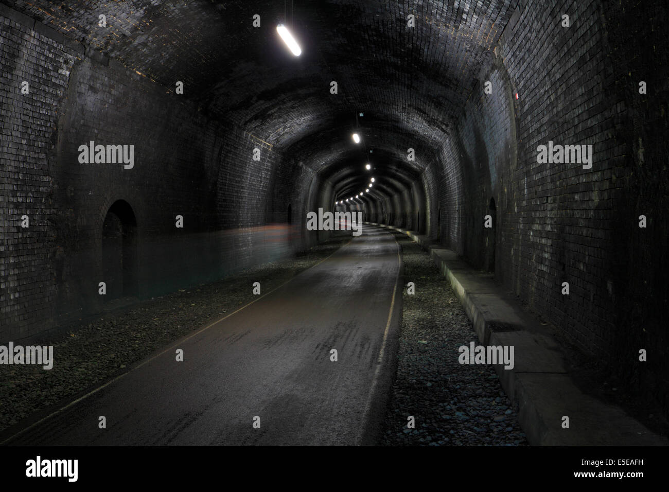 Cyclists motion blur in Headstone Tunnel on the Monsal Trail, Derbyshire, Peak District National Park, England, - Stock Image