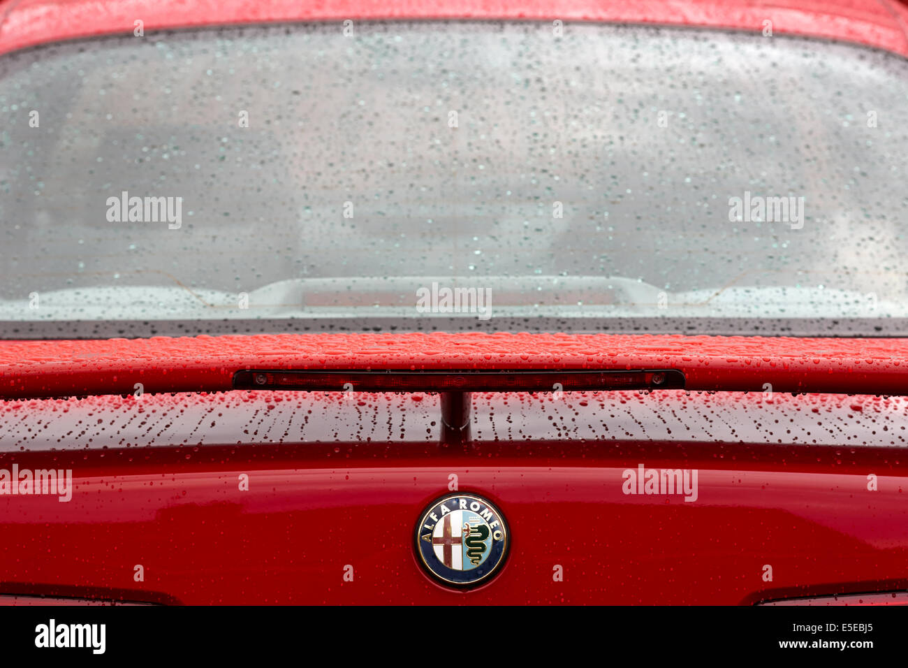 rear spoiler and raindrops on a red Alfa Romeo 156 - Stock Image