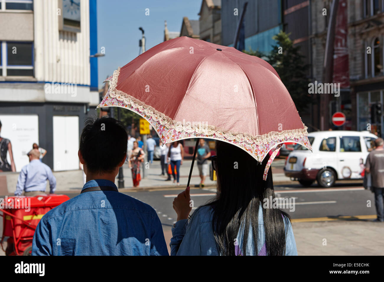 male and female asian tourist couple using a parasol on a hot sunny summers day in Belfast city centre - Stock Image