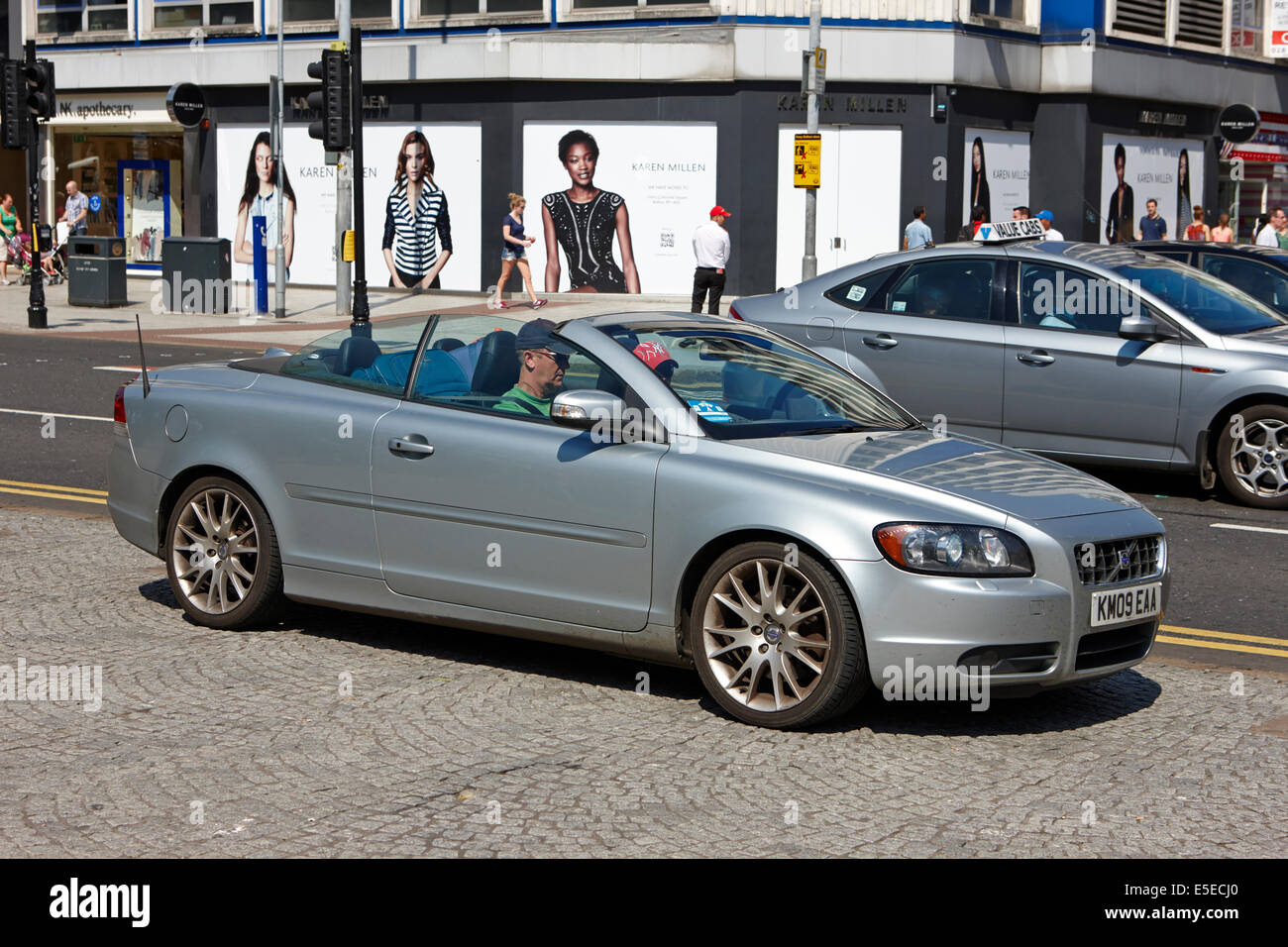 man driving a volvo convertible car on a bright sunny day Belfast city centre - Stock Image