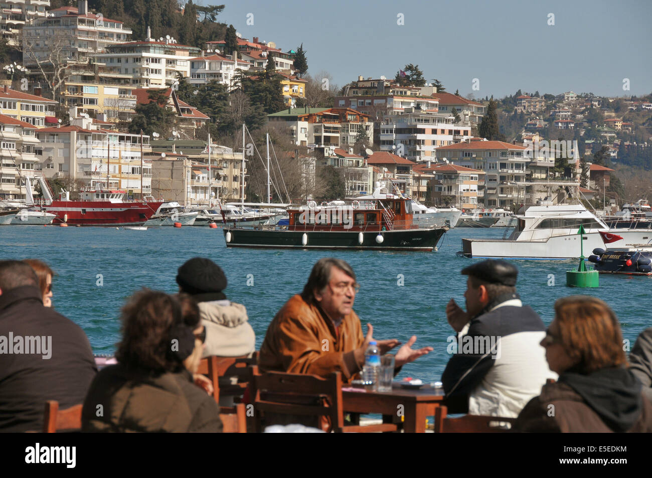 People enjoy a Sunday morning in March at the terrace of a cafe on the European shore of the Bosphorus in Bebek, Stock Photo