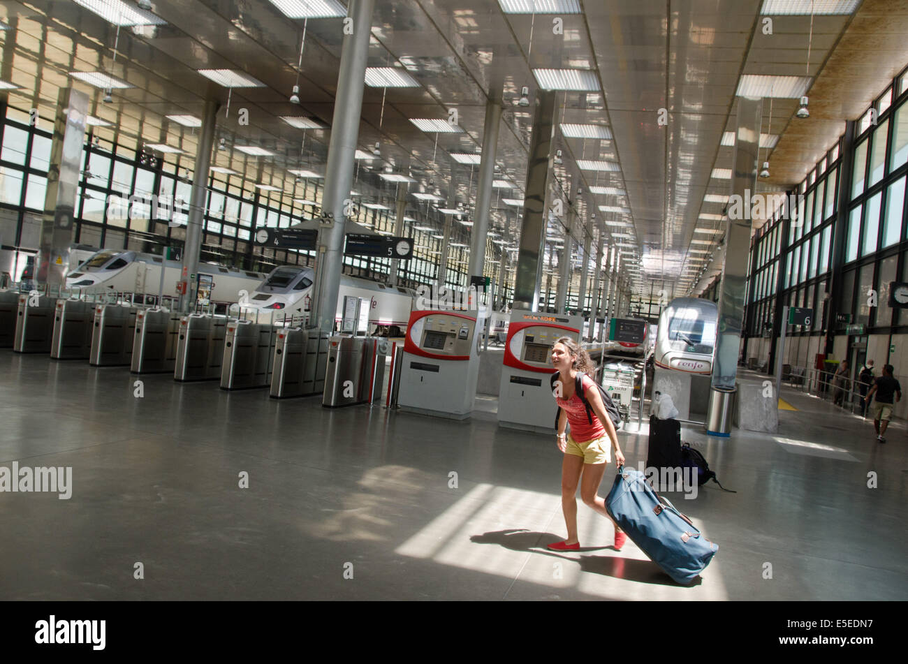 A young female traveller hurries across Cádiz train station with her luggage. - Stock Image