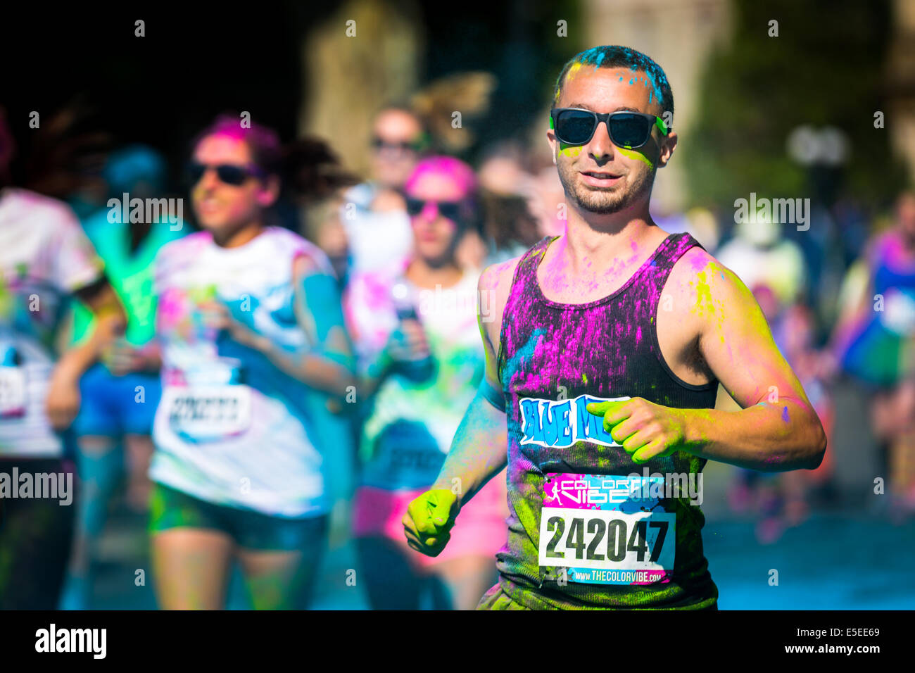 Young man runs the Color Vibe 5K race. Color Vibe is a fun un-timed event with no winners or prizes where runners - Stock Image