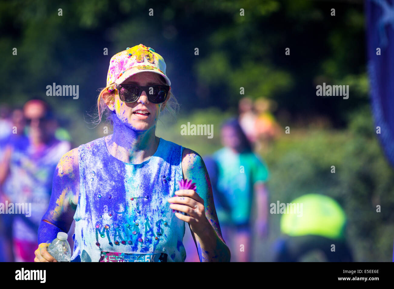Young woman runs the Color Vibe 5K race - Stock Image