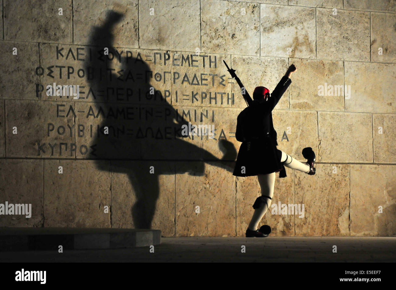 An 'Evzones' soldier in traditional uniform performs an elaborate martial marching routine during the  Sunday evening Stock Photo