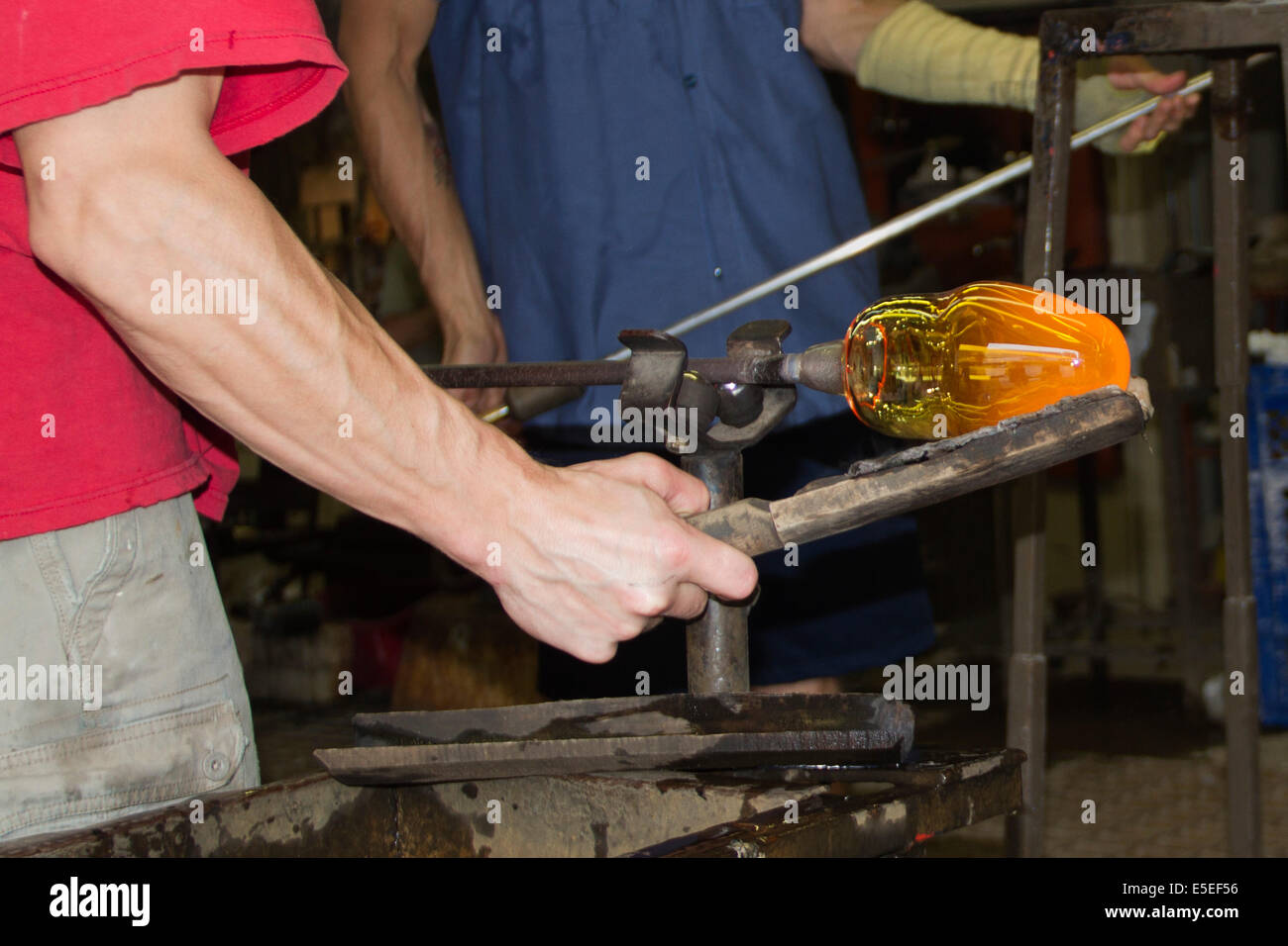 Glass blower uses a tool to help shape molten glass into a vase.Halifax,Nova Scotia,Canada - Stock Image