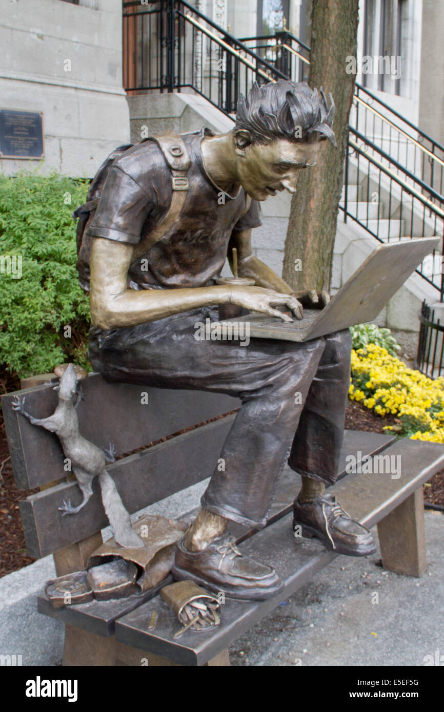 Humerous statue of student working on a computer while a squirrel steals his food located on a public street nar - Stock Image