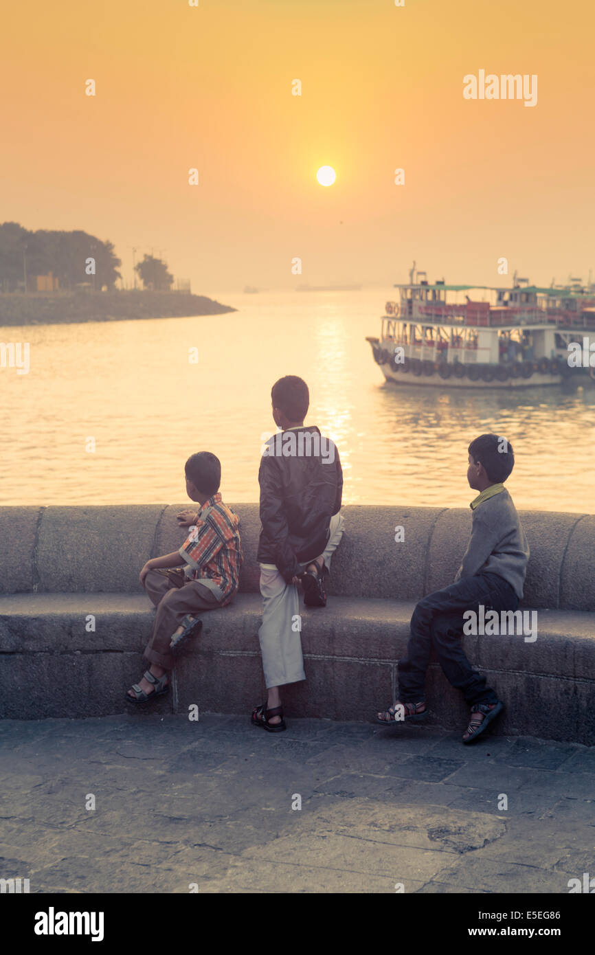 Children looking out over the docks in Mumbai at dawn, India - Stock Image
