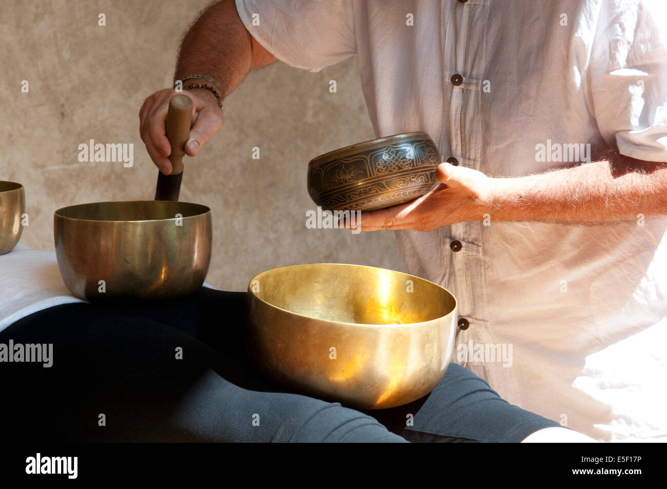 Tibetan Bells Therapy, Singing Bowl in the Hands of a Therapist - Stock Image
